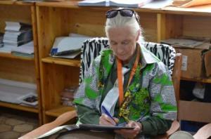 Jane Goodall portant la médaille laisse ses impressions dans le livre d'or du PNKB